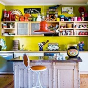 a fun and colorful kitchen with mustard walls, open and closed storage units, a shabby chic kitchen island and stools plus lots of decor and accessories