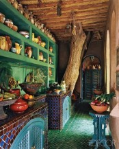 a bright vintage kitchen in green, with bold tile clad cabinets, a green tile floor and Moroccan decor is super bold