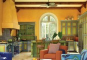 a colorful vintage kitchen in yellow, green cabinetry, blue cabinets, a large yellow hood and an orange chair