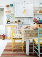 a cheerful ktichen with white cabinetry, bold yellow and blue chairs, floral textiles feels country and very relaxed