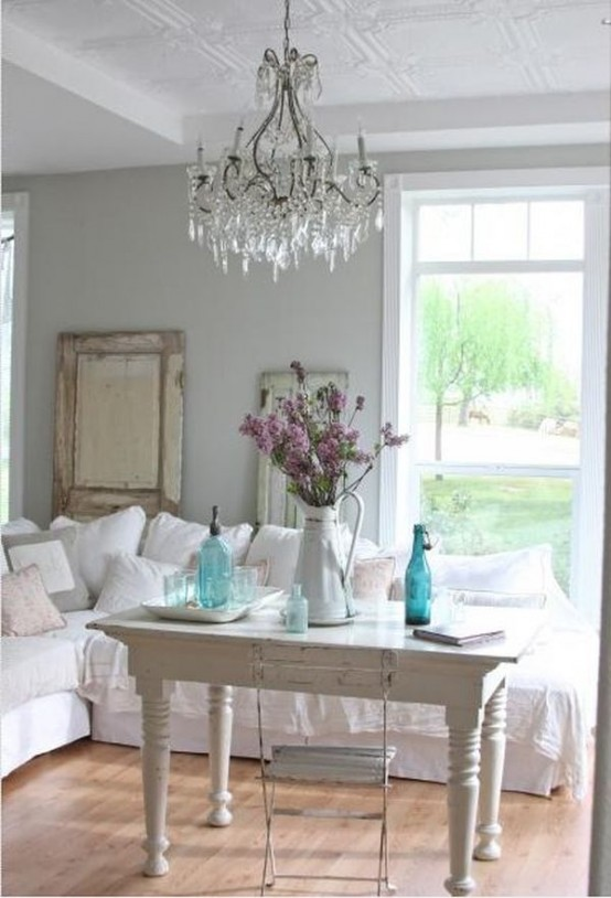 This large sofa is just as comfy as is swanky. A vintage table provides a perfect place to display a beautiful jug centerpiece.