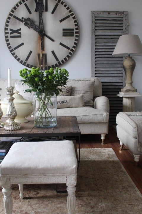 Large vintage wall clock with rust on them mixed with neutral furniture is a great way to make a farmhouse living room looks really interesting.