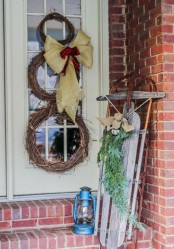 a snowman made of vine wreaths, with a burlap and plaid bow, a vintage sleigh with a burlap bow and fir branches plus a blue lantern for a rustic feel