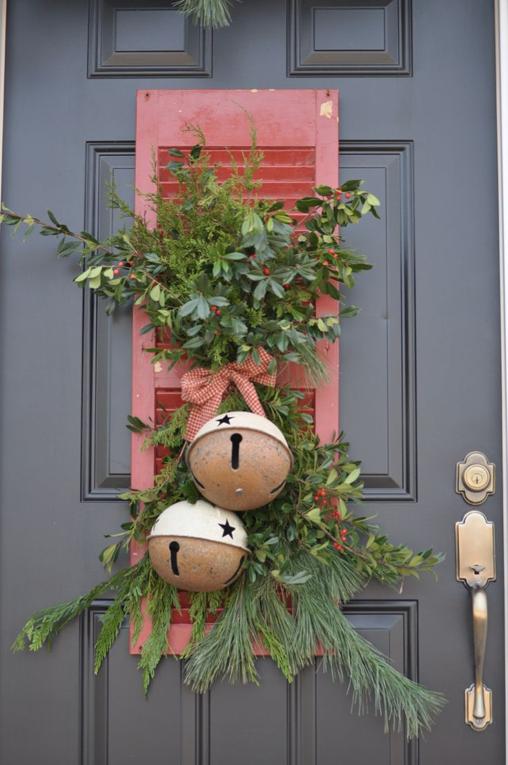 lovely and chic rustic front door decor with greenery and fir branches, berries, a plaid bow and oversized bells with stars