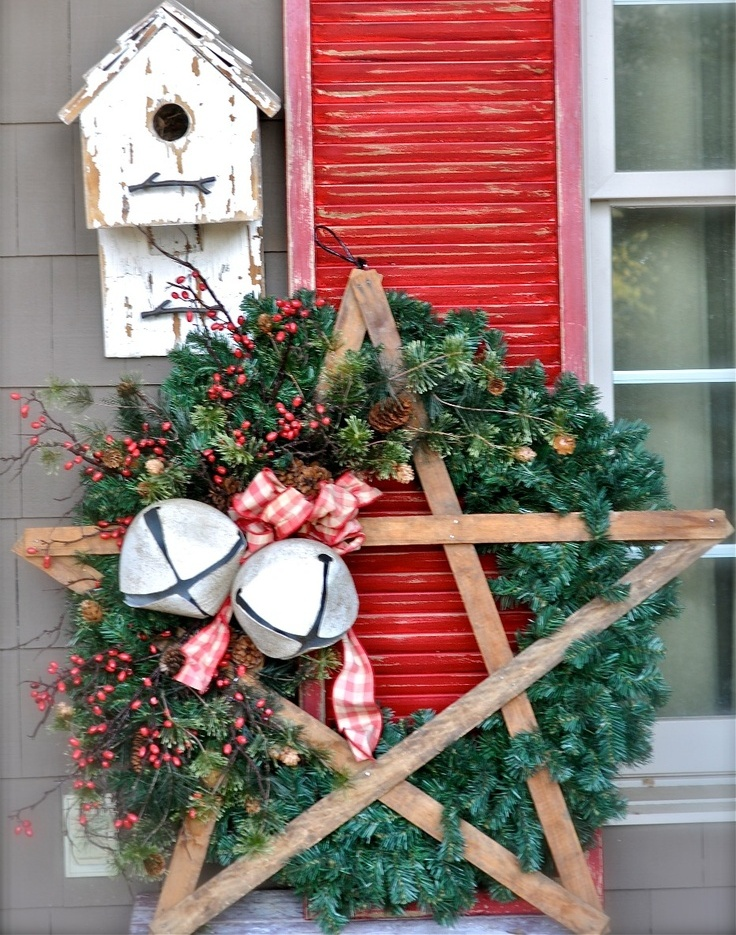 a fir wreath with berries and pinecones, a wooden star, oversized bells and plaid bows plus a bird house