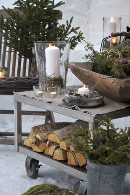 Nordic Christmas decor with firewood, fir branches, moss, candles is a great idea for a rustic and all natural feel in your outdoor spaces