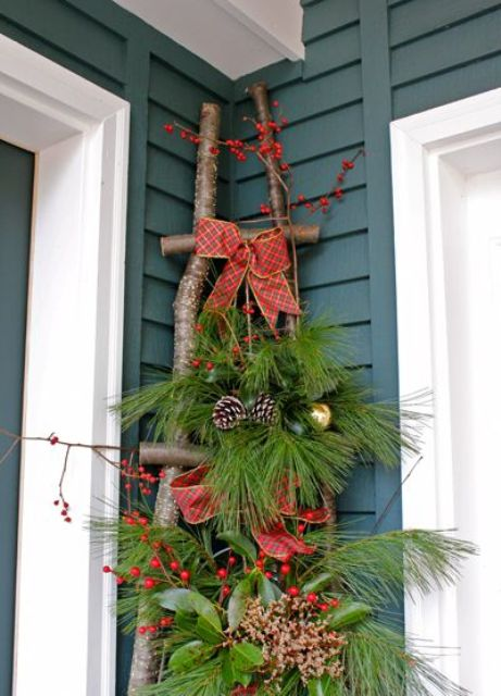 a ladder of branches, fir branches, pinecones, berries, red bows and metallic ornaments for rustic front porch decor