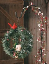 a fir branch sphere, with a candle, berries, a red bird on a stand interwoven with berries and greenery is chic