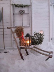 a rustic decoration – a lounger with dried herbs, a lantern, fir branches in a pot and a window frame with a vine heart for your backyard or front one