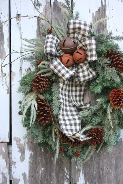 a fir wreath with pinecones, a plaid bow with bells and twigs is a chic and easy outdoor Christmas decoration