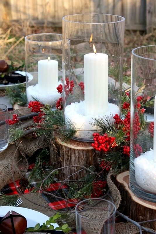 this candle decoration on a wood log with mistletoe and burlap is perfect for a lovely outdoor table setting