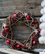 a gorgeous rustic Christma swreath of vine, pinecones, apples, berries and wooden stars is perfect for Scandi winter decor