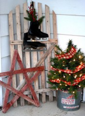 a wood plank star, a wooden door with skates, a mini Christmas tree with lights and burlap ribbons in a bucket for a rustic and vintage feel
