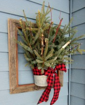 a frame with a bucket with fir branches and a red plaid bow is an easy DIY decoration for your front door or wall