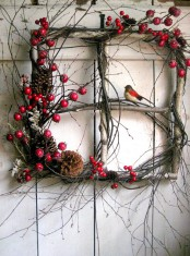 a window frame made of berries, twigs, pinecones and birdies looks very natural and very bright
