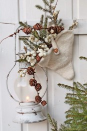 a lantern, a white cone with berries, fir branches with pinecones for delicate and chic vintage rustic decor