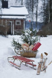 a red sleigh, skis, a basket with a Christmas tree and gifts for a cozy rustic feel in the space