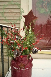 a red milk churn with greenery, berries, pinecones and a red star for a slight rustic and vintage feel in the space