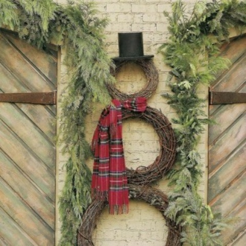 a snowman made of vine wreaths, a plaid scarf and a tall hat plus fir branches around for a slight rustic feel