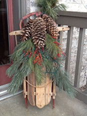 a vintage sleigh with fir branches, berries and oversized pinecones is a lovely rustic decoration for your front porch