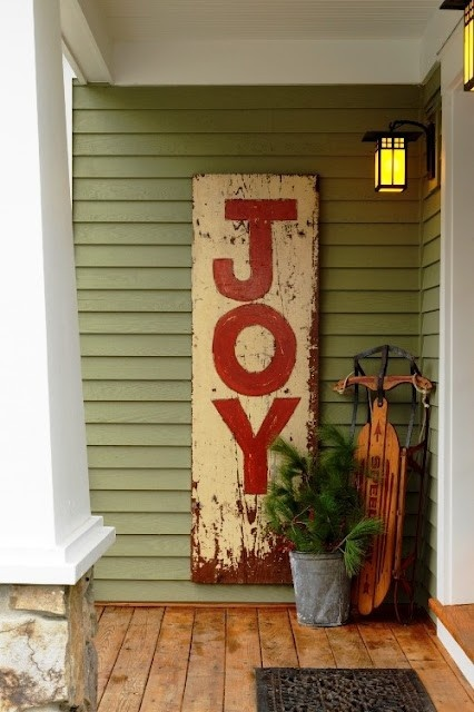 a shabby chic JOY sign, a bucket with fir branches and a vintage sleigh will make your front proch cozy and rustic