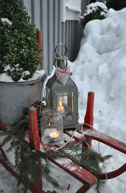 a red  sleigh with candle lanterns, a plant in a bucket and some fir branches is a lovely and chic idea for outdoor Christmas decor with a rustic feel