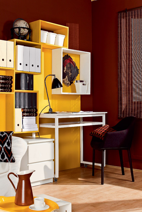 compact home office in a living room with a bright yellow storage wall
