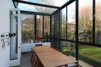 contemporary narrow sunroom extension that features black shutters