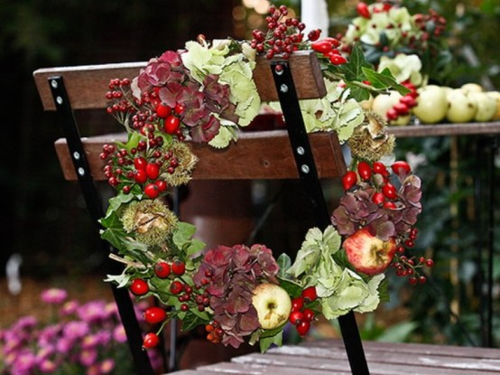 a fall or Thanksgiving wreath of greenery, berries, apples and dark blooms is a chic and very holiday-embracing idea