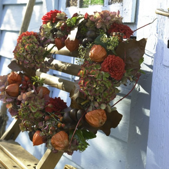 a moody Thanksgiving wreath of dried blooms and fresh greenery plus berries is a textural and lovely idea for the fall or Thanksgiving and it looks very natural