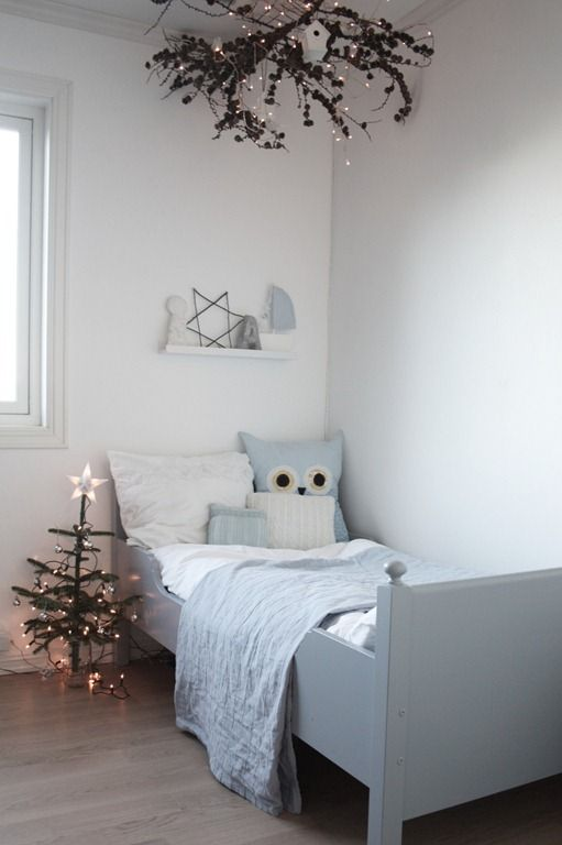 a simply decorated Christmas tree and some branches with pinecones and lights over the bed for a cozy holiday ambience in the room
