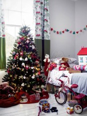 a neutral kid's room decorated for Christmas wiht a beautiful Christmas tree, garlands and banners, bold color block curtains and Christmas-inspired plush toys
