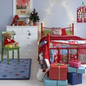 colorful Christmas bedding and a patchwork blanket, red decor, an advent calendar and bright gift boxes will make the kid's room Christmassy