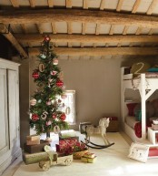 a Christmas tree with amazing red and white ornaments and gold letters plus printed and bold gift boxes stacked under the tree