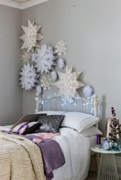 beautiful laser cut powder blue and white stars on the wall and some lights on the bed make the space look dreamy and very cute