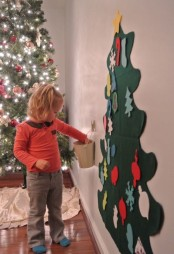 a felt wall-mounted Christmas tree decorated with felt letters and numbers and other ornaments that you can make together with your kids
