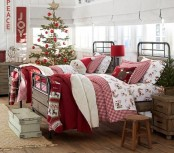 a Christmas tree decorated with red ornaments, red and white signs on the wall and printed Christmassy bedding for a holiday feel