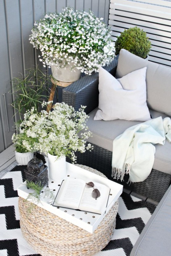 a summer Scandinavian terrace in black and white, with dark furniture, blooms and greenery in pots and a cool ottoman