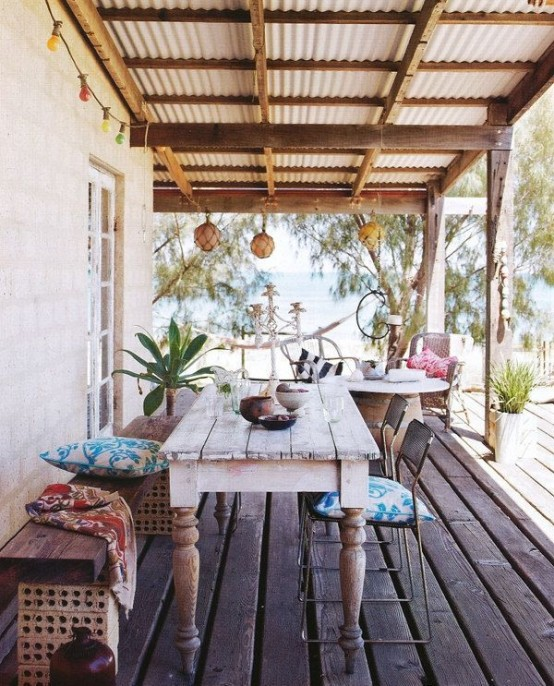 a bright tropical summer terrace with a whitewashed table, a carved wooden bench, metal chairs and textiles and lanterns attached to the roof