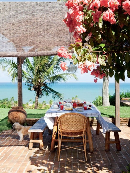 a bright summer terrace with lots of blooms and palm trees, with wooden furniture and rattan chairs, with a gorgeous sea view