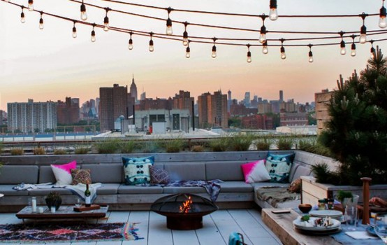 a rooftop summer terrace with a large built-in bench, tables and a fire pit, colorful pillows and string lights over the space