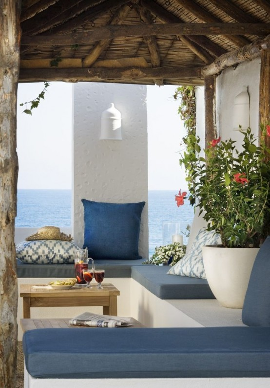 a seaside summer terrace in white, with blue textiles and upholstery, potted blooms and greenery and a cool seaside view