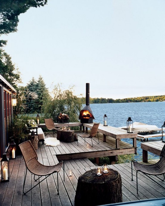 a riverside deck with wicker chairs, a fireplace, candle lanterns, stump tables and a cool riverside view