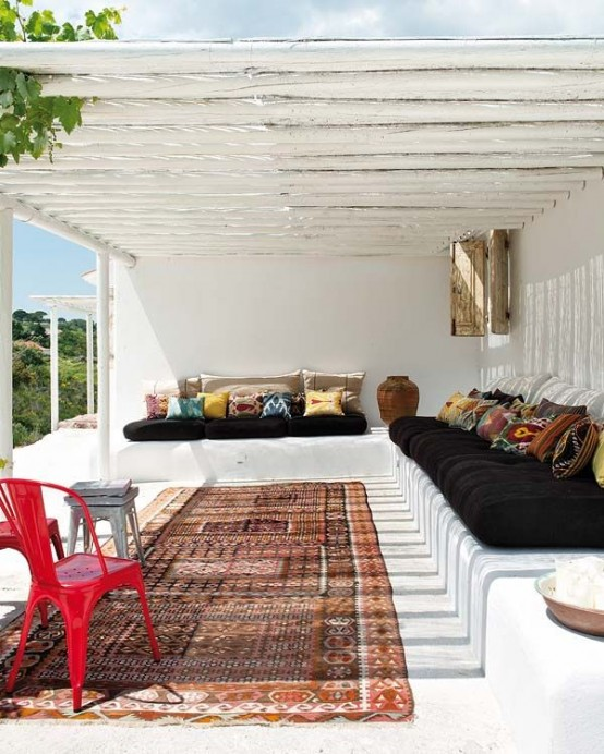 a white summer terrace with a built-in bench, dark upholstery and colorful pillows, a boho rug and a cool sea view
