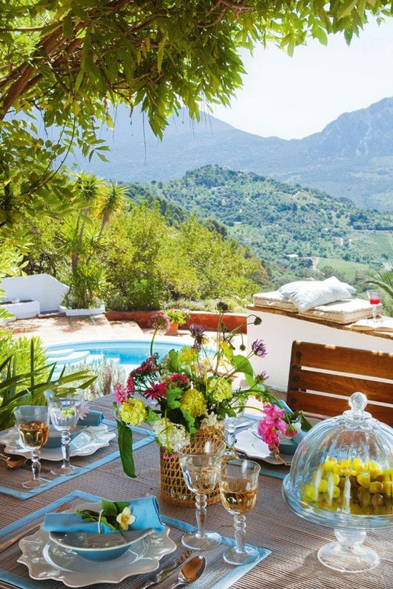 a bright summer terrace by the pool, with cushions and pillows and a bright dining zone with bold blooms and placemats with blue edges