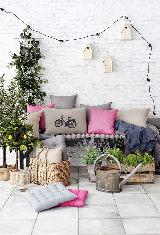 a bright and fun summer terrace with a black bench, colorful pillows, pallets and boxes with greenery and blooms, a garland and birdhouses for decor