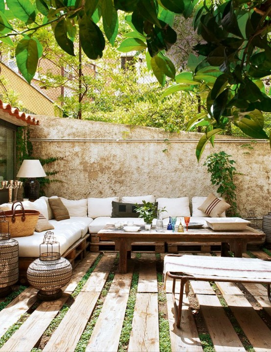a welcoming Mediterranean summer terrace with pallet and rattan furniture, neutral upholstery and textiles, candle lanterns and greenery