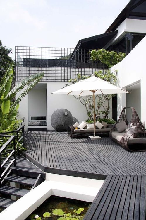 a monochromatic Scandinavian terrace with a black deck, dark rattan furniture, lots of greenery and a tree plus a little pond