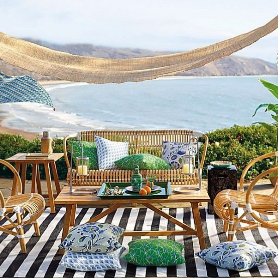 a bright and bold summer terrace with a cool sea view, a striped rug, rattan furniture, colorful textiles is super welcoming
