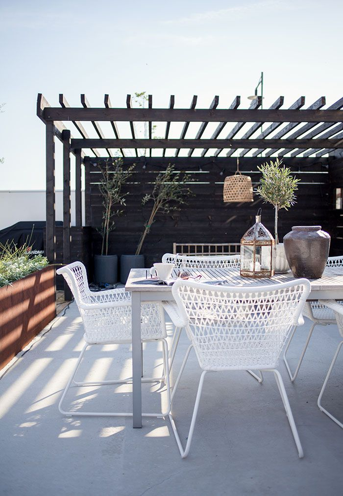 a monochromatic summer terrace with potted greenery and trees, white furniture of metal and wood, candle lanterns